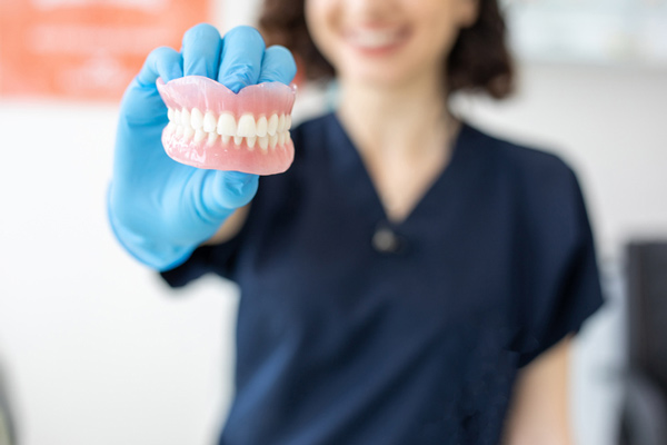 Woman holding a set of dentures for a patient with missing teeth at Revive Dental and Implant Center in Charleston, WV.