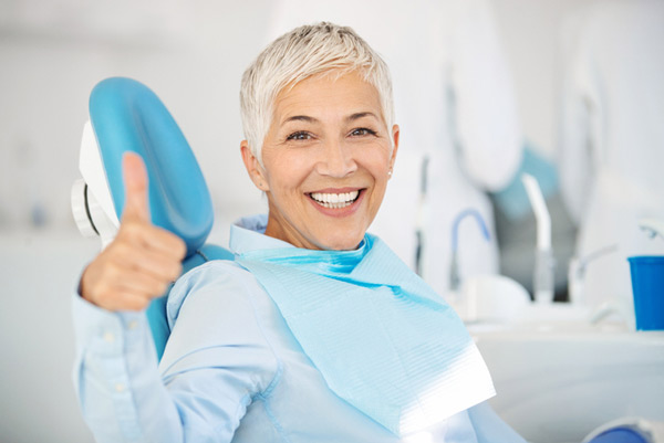 Mature woman smiling in a dental chair at Revive Dental and Implant Center in Charleston, WV